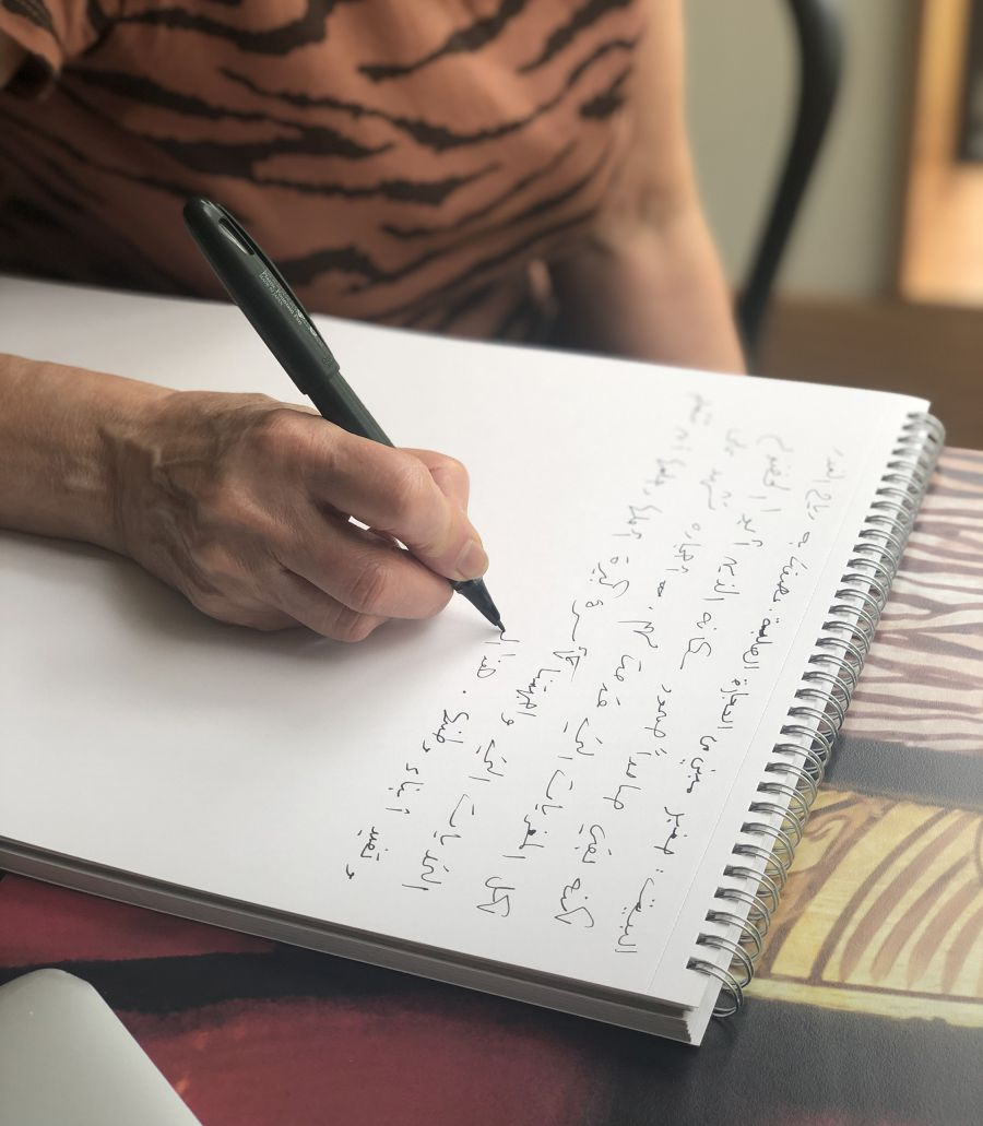Woman writing in Arabic on a notepad