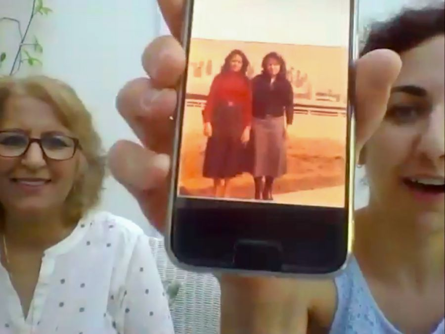 A mother and daughter share photos on a mobile phone