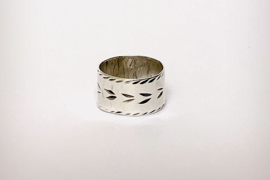 Silver ring with markings on a plain background