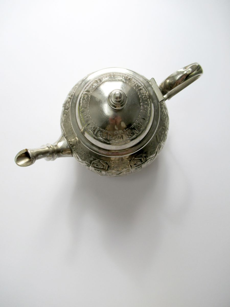 Photo of a silver teapot from above