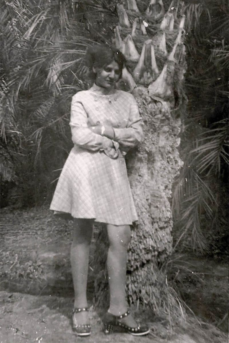 Archive photo of a woman in a dress standing against a tree