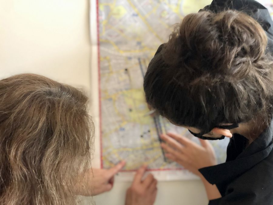 Two figures draw over a map