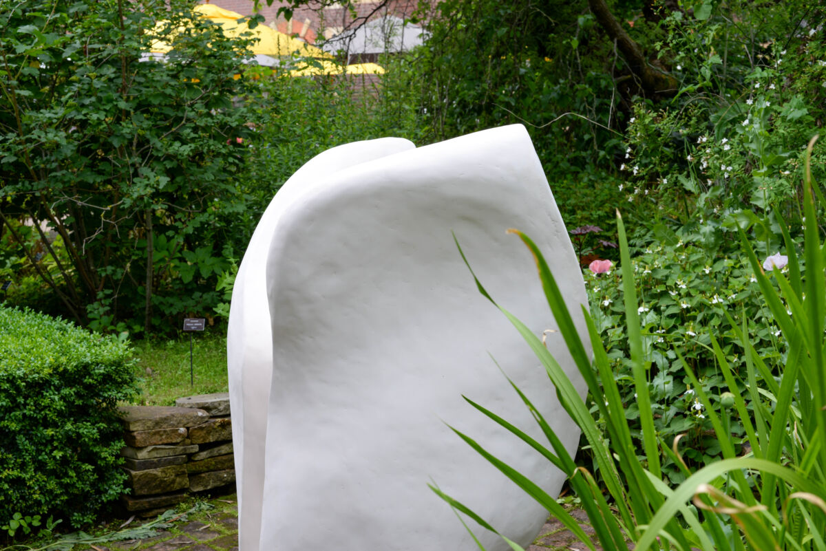 white abstract sculpture in a garden setting